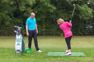 女性が男性にゴルフを教わっているイメージ